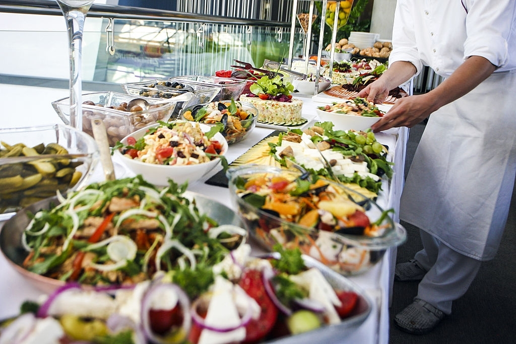Waiter serving a large buffet table full of delicious food. Unrecognizable Caucasian male, professional in white apron and uniform.